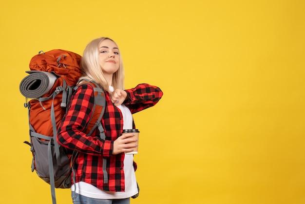 Widok z przodu pewna blondynka z jej plecakiem trzymając filiżankę kawy