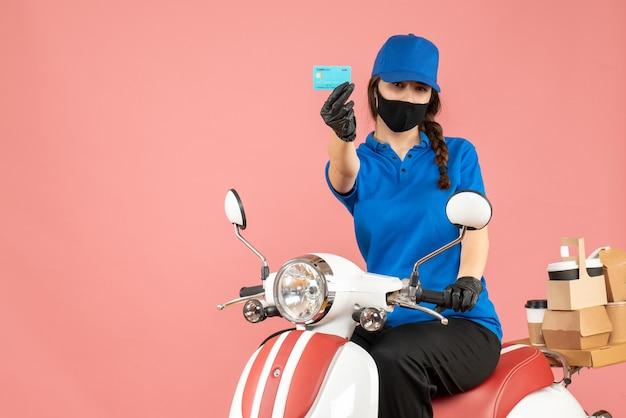 Widok z przodu pewnie kurierska dziewczyna ubrana w maskę medyczną i rękawiczki, siedząc na skuterze, trzymając kartę bankową dostarczającą zamówienia na pastelowym brzoskwiniowym tle
