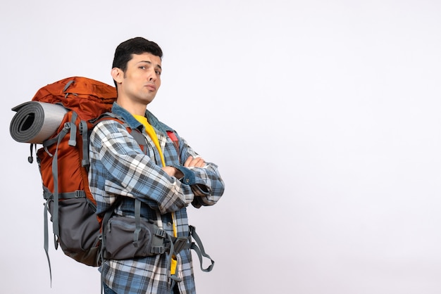 Widok z przodu pewny podróżnik z plecakiem, skrzyżowanymi rękami