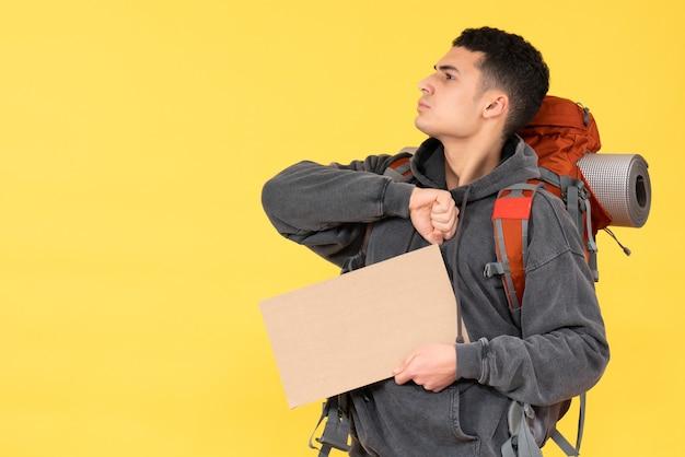 Widok z przodu pewny siebie młody człowiek z czerwonym plecakiem trzymając karton