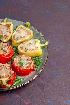 Widok z przodu pieczona papryka z serem i mięsem wewnątrz talerza na ciemnym tle jedzenie piec obiad danie posiłek