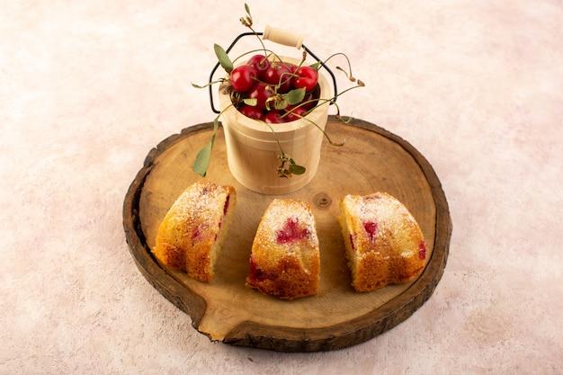 Widok z przodu pieczone ciasto owocowe pyszne pokrojone w czerwone wiśnie w środku i cukier puder na drewnianym biurku ze świeżymi wiśniami na różowo