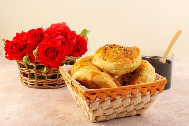 Widok z przodu pieczone qogals wschodnie pieczone bułeczki świeże gorące wewnątrz pojemnika na chleb wraz z czerwonymi kwiatami i pieprzem na stole i różowym