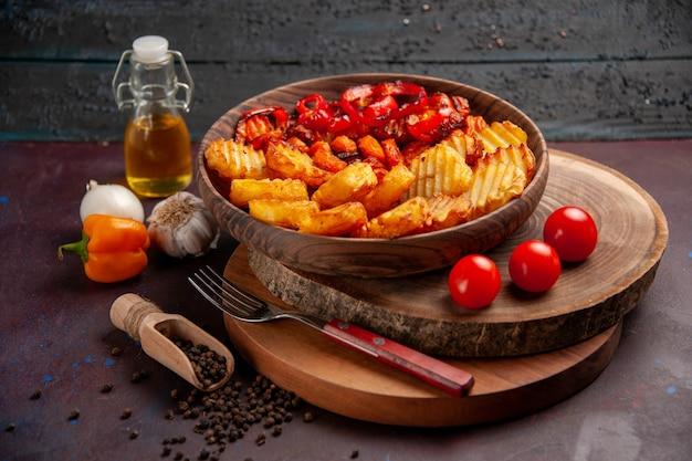 Widok z przodu pieczone ziemniaki z gotowanymi warzywami na ciemnym miejscu