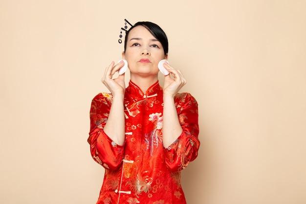 Widok z przodu piękna japońska gejsza w tradycyjnej czerwonej japońskiej sukience z paskami do włosów stwarzających trzymanie małej białej bawełny elegancko na kremowej ceremonii w japonii