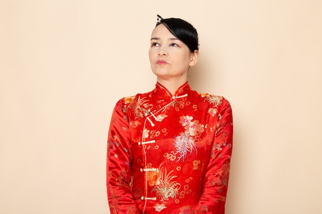 Widok z przodu piękna japońska gejsza w tradycyjnej czerwonej japońskiej sukience z paskami włosów, stojąc na kremowej ceremonii zabawnej japonii