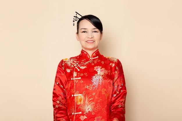 Widok z przodu piękna japońska gejsza w tradycyjnej czerwonej japońskiej sukni z włosami wystającymi stojąc na kremowym tle uśmiechnięta ceremonia zabawna na wschodzie japonii