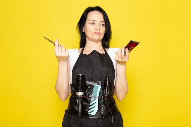 Widok z przodu piękna kobieca fryzjerka w białej koszulce z czarną peleryną ze szczotkami z umytymi włosami trzymająca nożyczki i maszynę pozującą na żółtym tle stylista fryzjer włosy