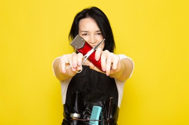 Widok z przodu piękna kobieta fryzjerka w białej koszulce czarna peleryna ze szczotkami z umytymi włosami trzyma nożyczki i uśmiecha się do maszyny na żółtym tle fryzjer fryzjer