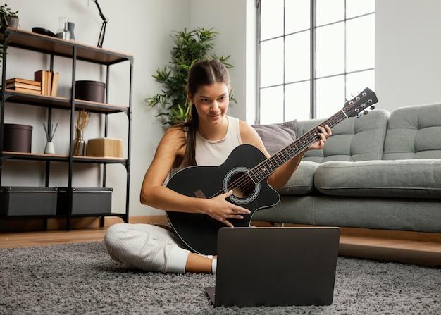 Widok z przodu piękna kobieta gra na gitarze