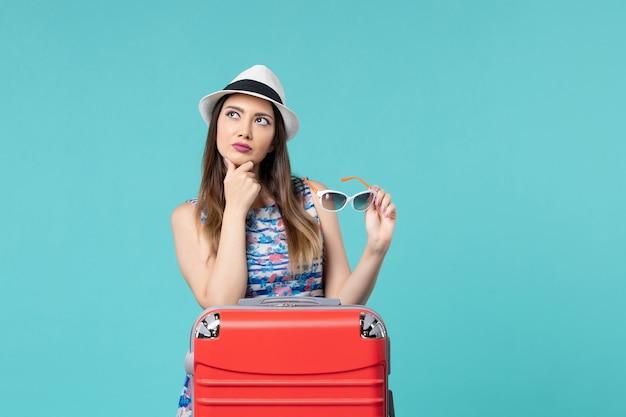 Widok z przodu piękna kobieta przygotowuje się do wakacji trzymając okulary przeciwsłoneczne, myśląc na niebieskiej przestrzeni