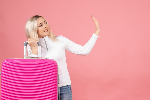 Widok z przodu piękna kobieta z przestrzennym gestem ręki trzymającej walizkę