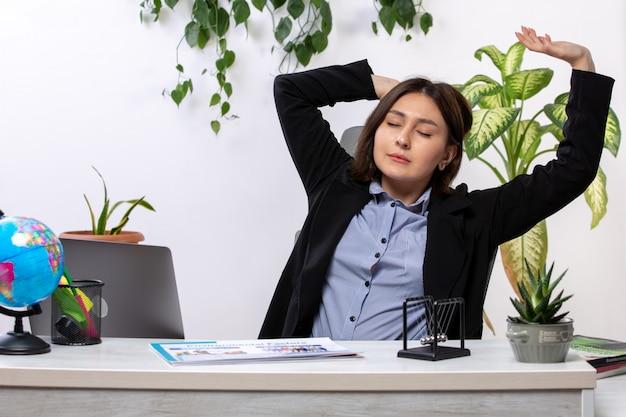 Widok z przodu piękna młoda bizneswoman w czarnej kurtce i niebieskiej koszuli kichanie przed biurowym urzędem pracy