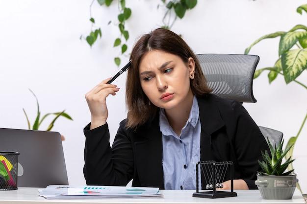 Widok z przodu piękna młoda bizneswoman w czarnej kurtce i niebieskiej koszuli myślenia przed biurowym urzędem pracy