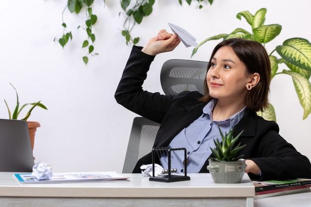 Widok z przodu piękna młoda bizneswoman w czarnej kurtce i niebieskiej koszuli uśmiecha się rzucając papierowe samoloty przed stołem pracy biurowej