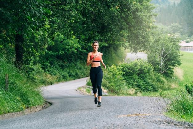 Widok z przodu piękne szczęśliwe kobiety biegające po drodze przez piękny zielony las z mnóstwem drzew
