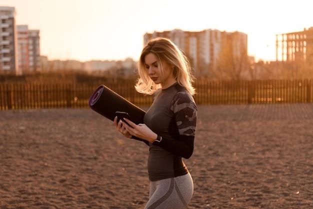 Widok z przodu pięknej kobiety w szarym stroju sportowym, patrzącej na telefon, trzymającej w drugiej ręce matę do jogi. kobieta idzie na plac zabaw do uprawiania sportu o zachodzie słońca.