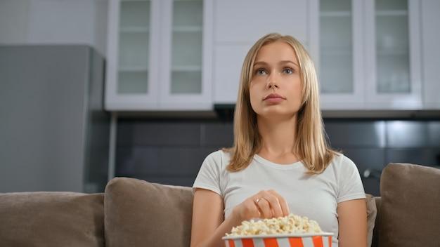 Widok z przodu pięknej kobiety z podziwem, oglądając telewizję i jedząc popcorn.