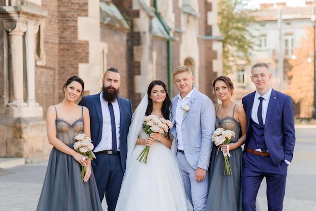 Widok z przodu pięknych nowożeńców z przyjaciółmi patrzącymi w kamerę i uśmiechającymi się na ulicy