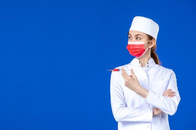 Widok z przodu pielęgniarka w białym garniturze medycznym z czerwoną maską i zastrzykiem w dłoniach na niebiesko