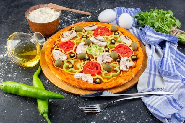 Widok z przodu pikantna pizza grzybowa z czerwonymi pomidorami, papryką, oliwkami i grzybami, całość pokrojona w plasterki z jajkami na szaro