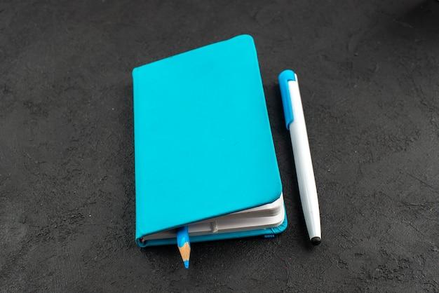 Widok z przodu pióra wewnątrz zamkniętego niebieskiego notatnika i pióra na czarno