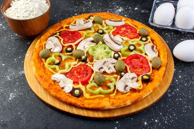 Widok z przodu pizza grzybowa z czerwonymi pomidorami, papryką, oliwkami i pieczarkami, całość pokrojona w jajka i mąkę na szaro