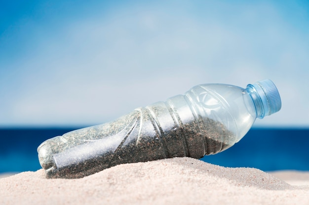 Widok z przodu plastikowej butelki na plaży z piaskiem