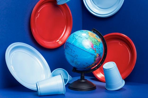 Widok z przodu plastikowych kubków i talerzy z kulą ziemską