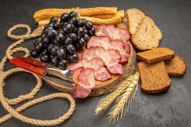 Widok z przodu plastry szynki z bułeczkami i kromkami chleba na ciemnym kolorze zdjęcie przekąski mięsne jedzenie posiłek