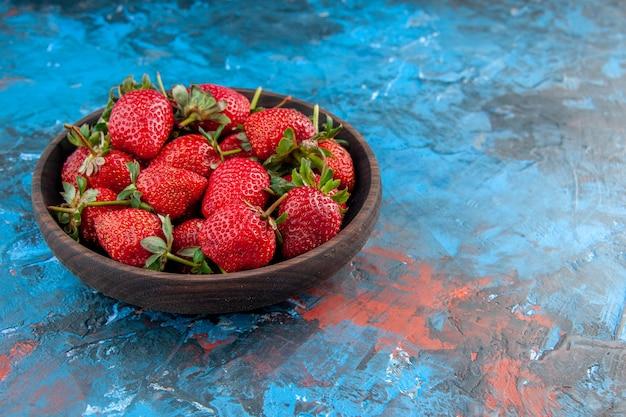 Widok z przodu płyta z truskawkami świeże smaczne dojrzałe owoce na niebieskim tle zdjęcie kolor drzewo jagodowe czerwone dzikie lato