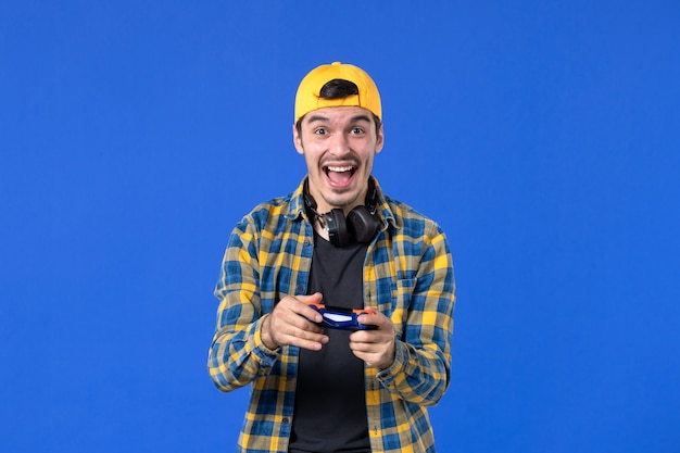Widok z przodu podekscytowanego męskiego gracza z gamepadem grającym w grę wideo na niebieskiej ścianie