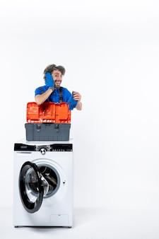 Widok z przodu podekscytowany mechanik przykładający rękę do ucha za pralką na białej przestrzeni