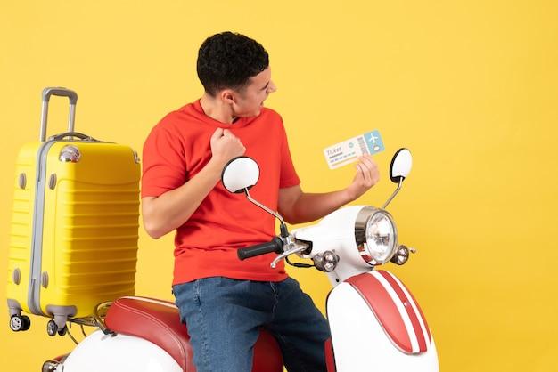 Widok z przodu podekscytowany młody mężczyzna w ubranie na bilet na motorower