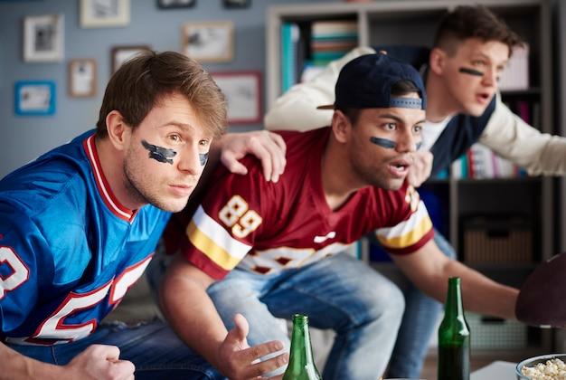 Widok z przodu podekscytowanych mężczyzn oglądających mecz sportowy