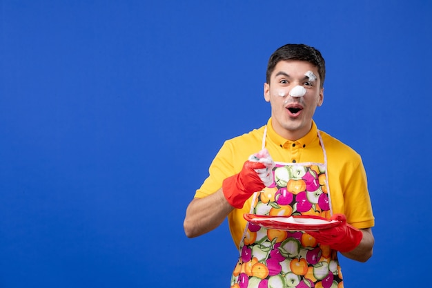 Widok z przodu podniecona męska gospodyni z pianką na talerzu do mycia twarzy na niebieskiej przestrzeni
