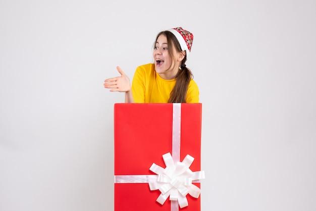 Widok z przodu podniecony dziewczyna z santa hat podając rękę stojącą za wielkim prezentem bożonarodzeniowym