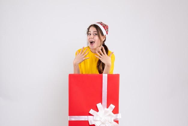 Widok z przodu podniecony dziewczyna z santa hat stoi za wielkim prezentem bożonarodzeniowym