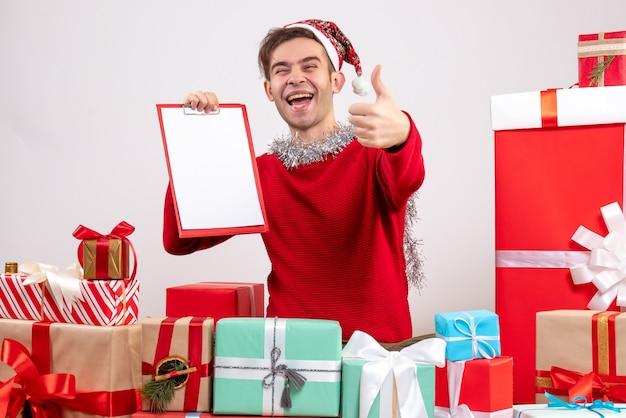 Widok z przodu podniecony młody człowiek siedzący wokół świątecznych prezentów