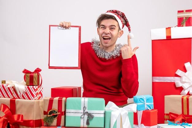 Widok z przodu podniecony młody człowiek trzymający schowek siedzący wokół świątecznych prezentów