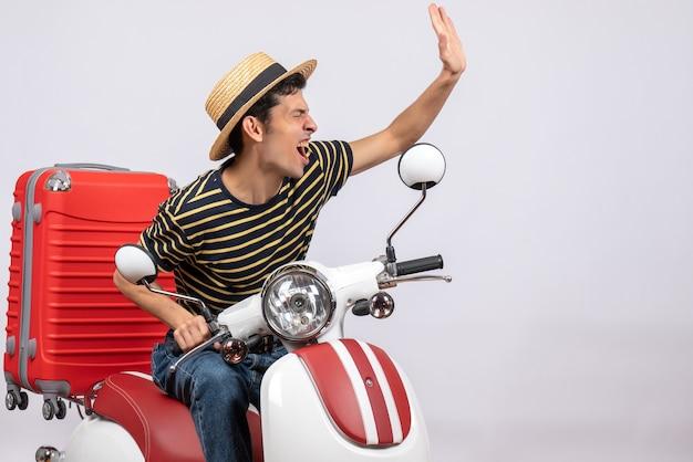 Widok z przodu podniecony młody człowiek ze słomkowym kapeluszem na motorowerze witając somene