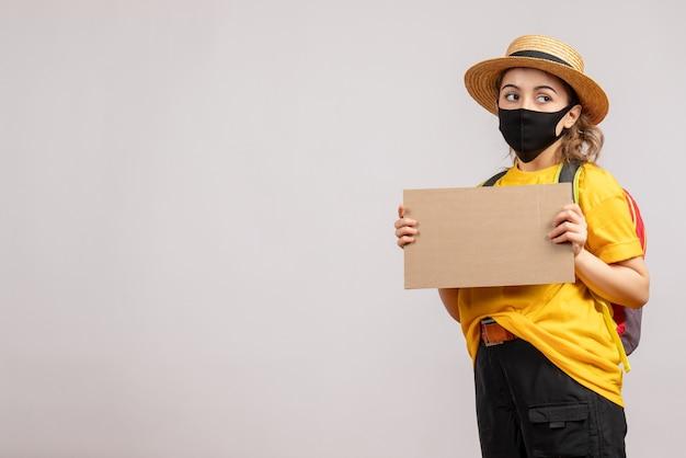 Widok z przodu podróżniczki z plecakiem trzymającym karton na szarej odizolowanej ścianie