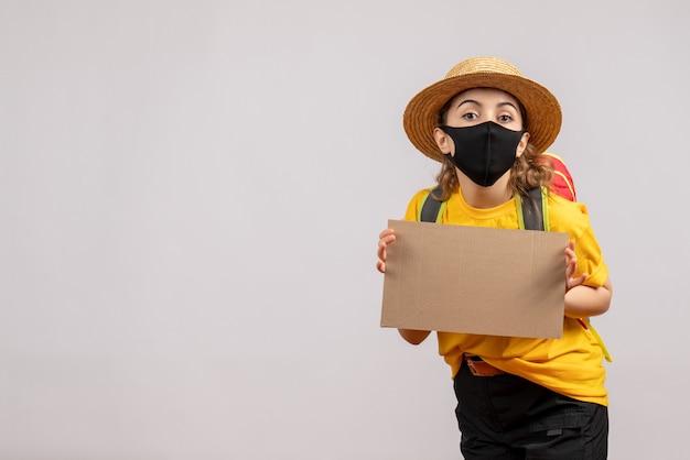 Widok z przodu podróżniczki z plecakiem trzymającym karton na szarej ścianie