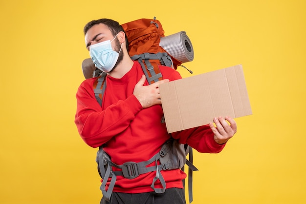 Widok z przodu podróżnika w masce medycznej z plecakiem pokazującym prześcieradło bez pisania na żółtym tle yellow