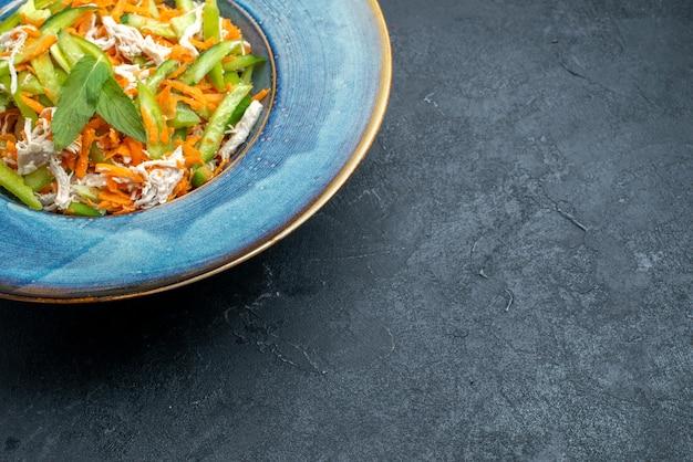 Widok z przodu pokrojona sałatka jarzynowa wewnątrz talerza na ciemnoszarym biurku