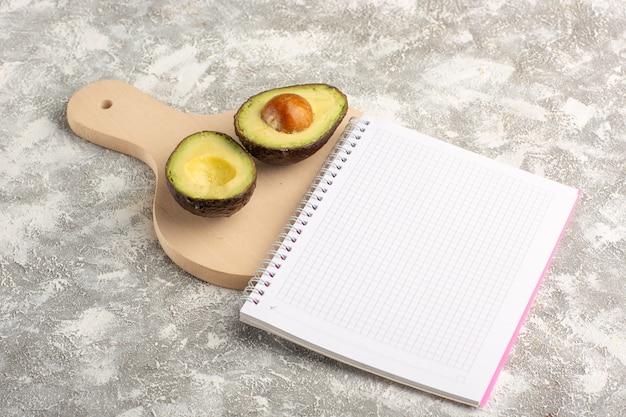 Widok z przodu pokrojone awokado z notatnikiem na białym biurku