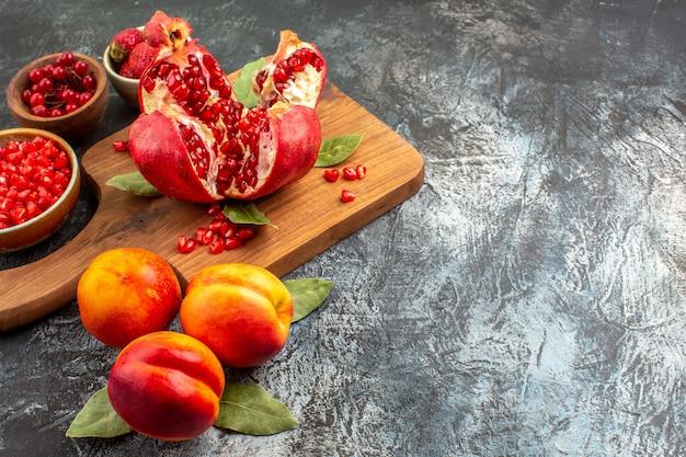 Widok z przodu pokrojone granaty z brzoskwiniami na ciemnym stole owoce drzewa ogrodowego
