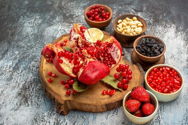 Widok z przodu pokrojone granaty z innymi owocami na jasno-ciemnym stole z owocami ogrodowymi