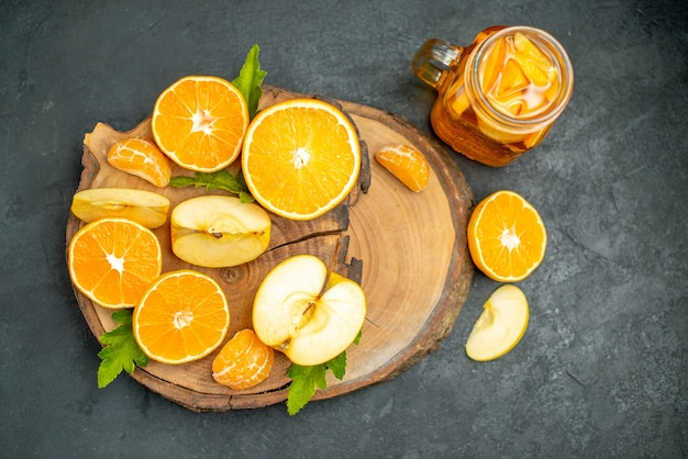 Widok z przodu pokrojone jabłka i pomarańcze na koktajlu na desce na ciemnym tle
