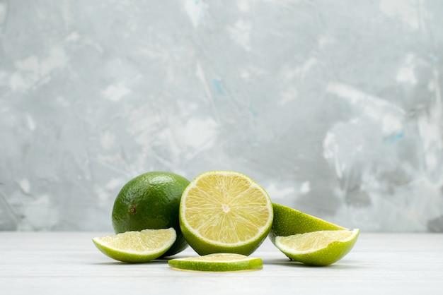 Widok z przodu pokrojone świeże limonki soczyste i kwaśne owoce na białym tle